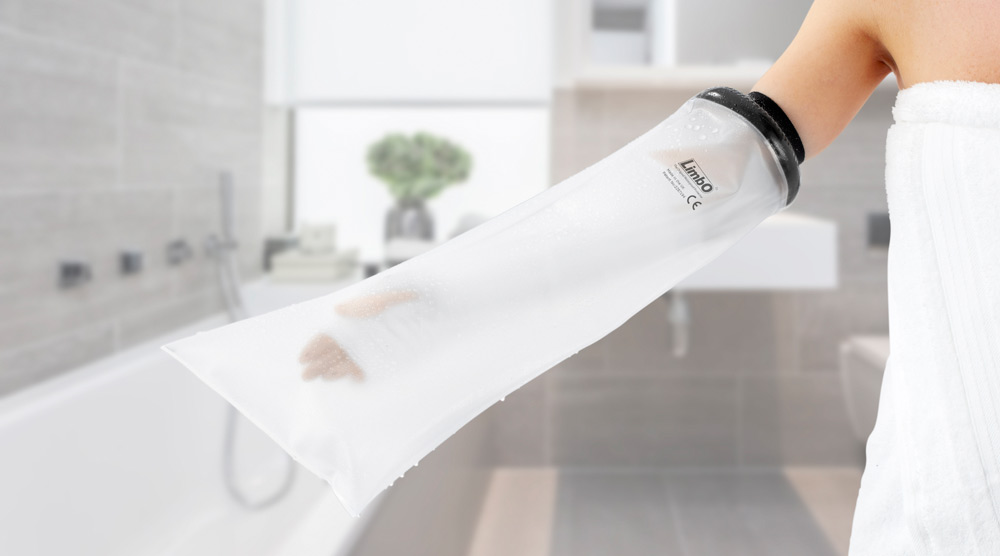 A woman in a bathroom wearing a half arm LimbO Waterproof Protector on her right arm